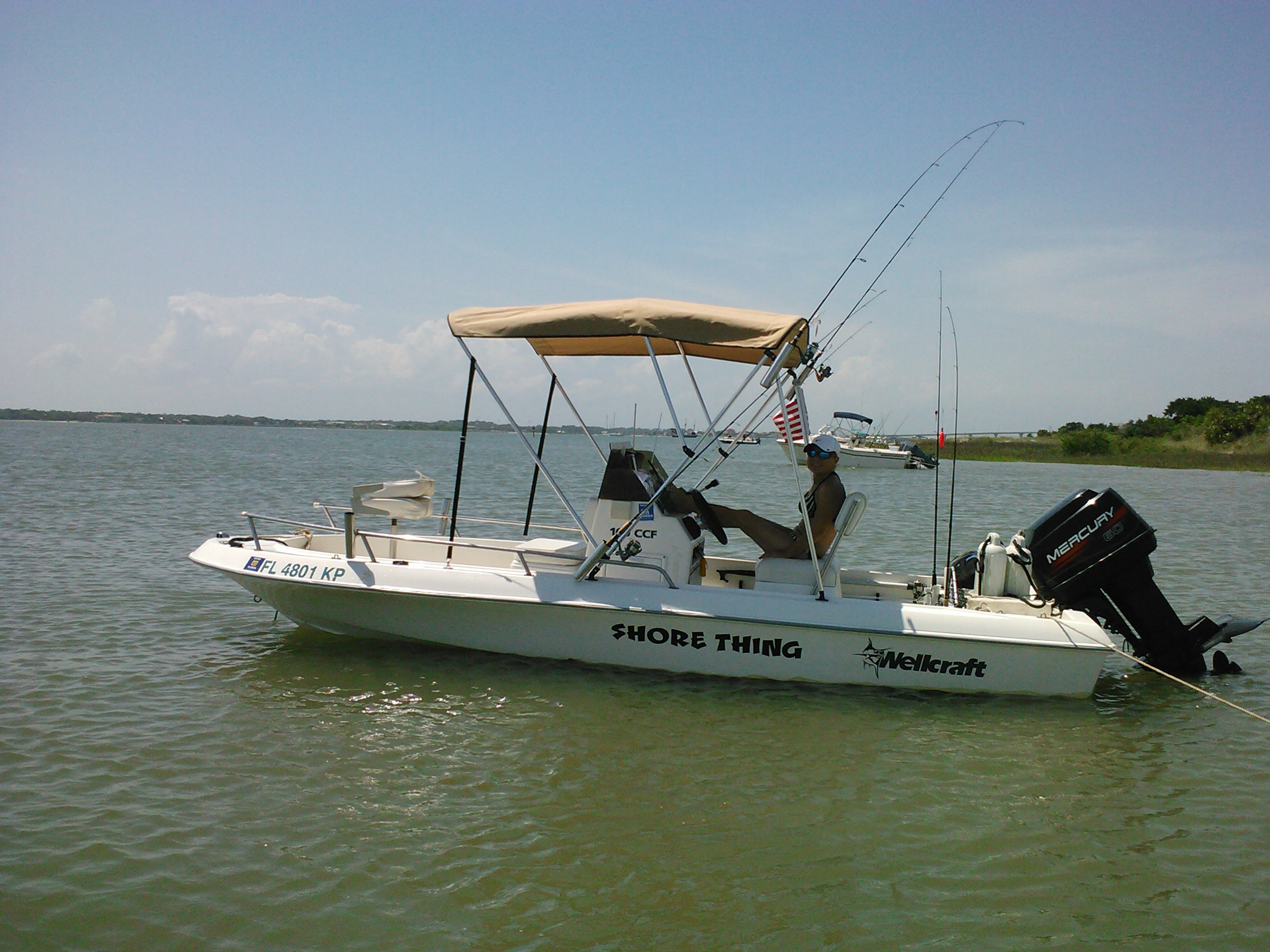 man sitting on his fishing boat under the Bimini top