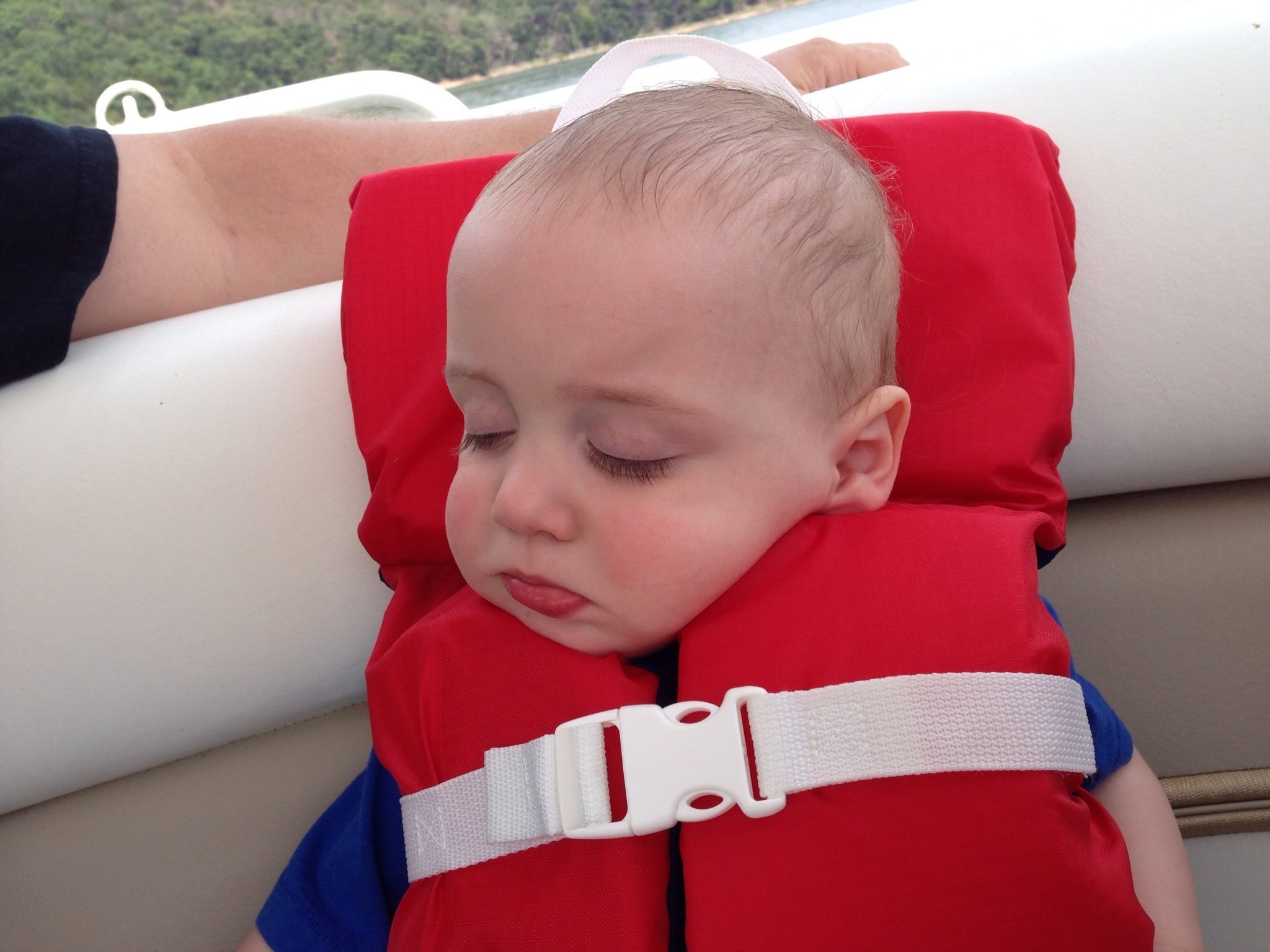 child with a life jacket on asleep in the boat