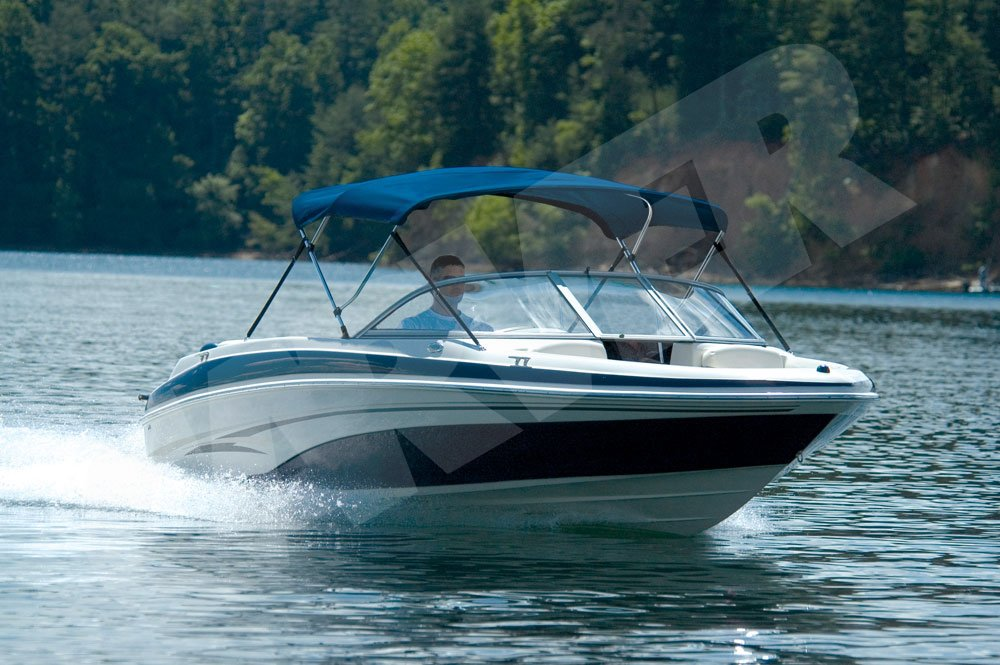man driving boat on lake with Bimini top up