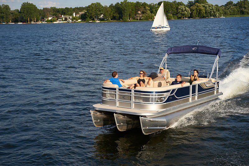 family on a pontoon boat riding down the lake