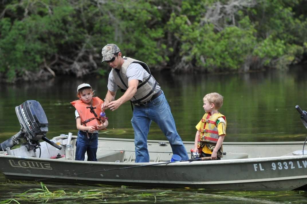 2 children and father in boat learning to fish