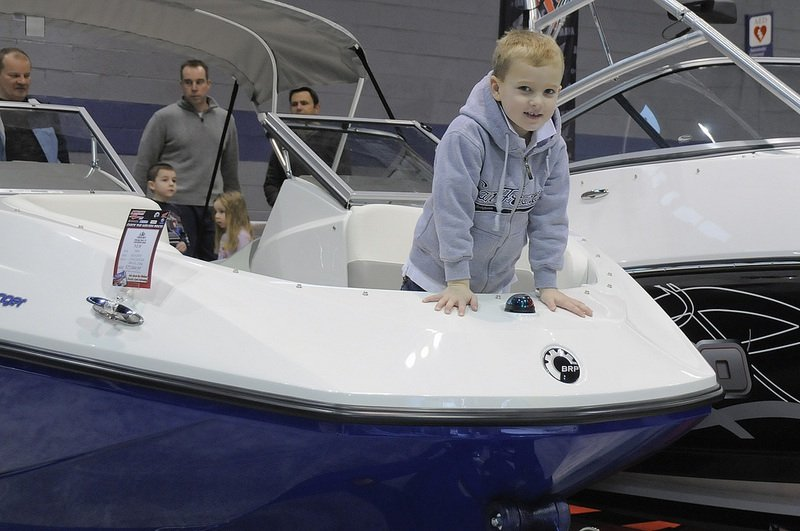 Cute Kid wearing Hoodie in Bow of Boat at Boat Show with Family